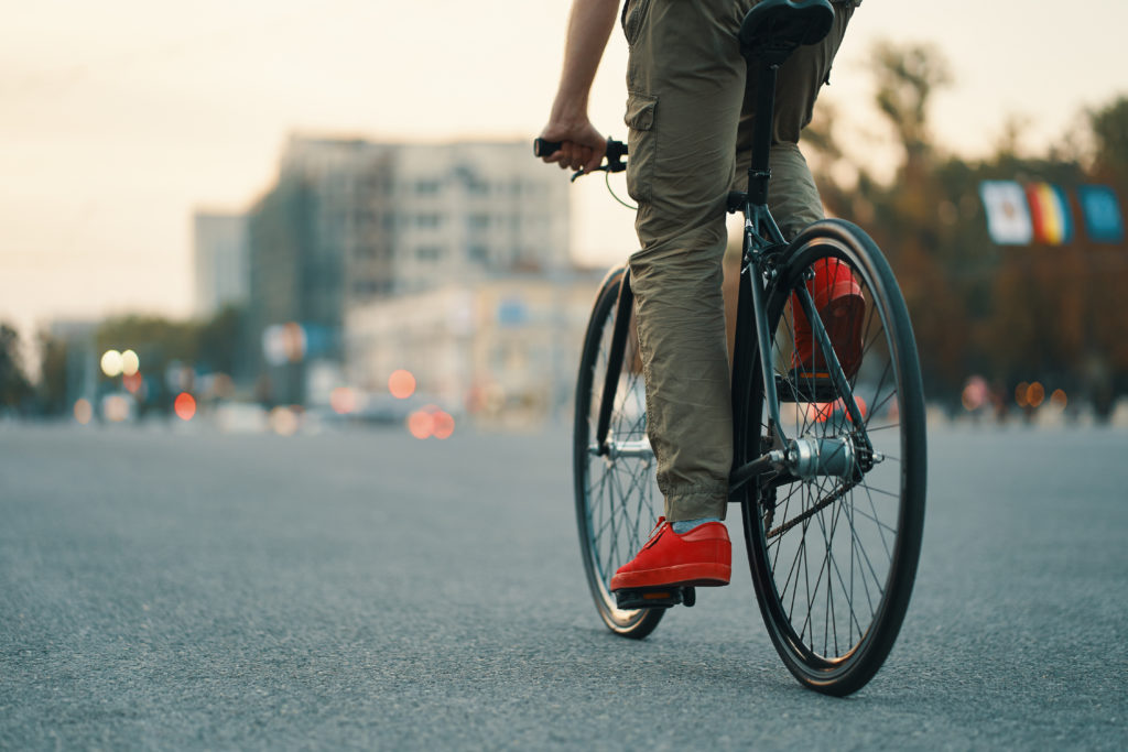 Closeup of casual man legs riding classic bike on city gray road wearing red sneakers and comfy pants. Copy space
