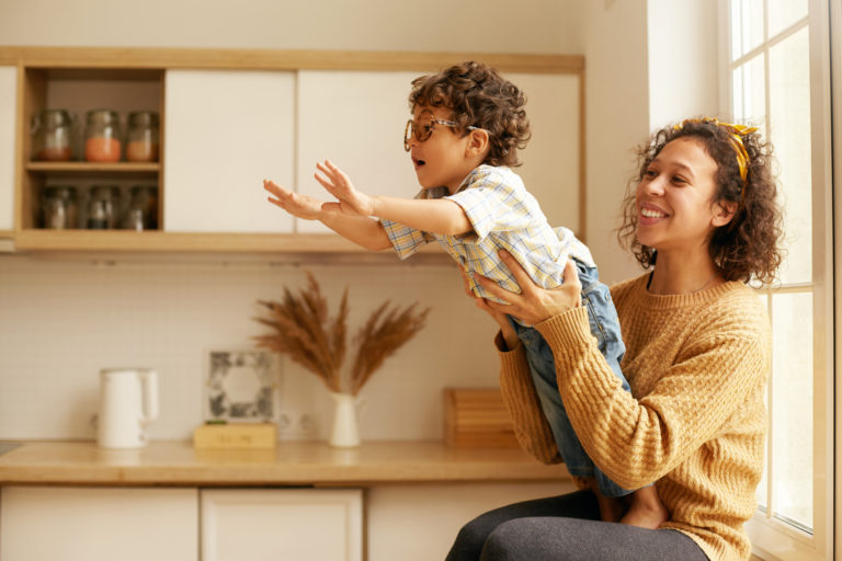 Portrait of cute young Latin woman in sweater sitting on wndowsill holding her two year old son who is reaching out hands as if flying. Happy mom and child playing in cozy kitchen interior